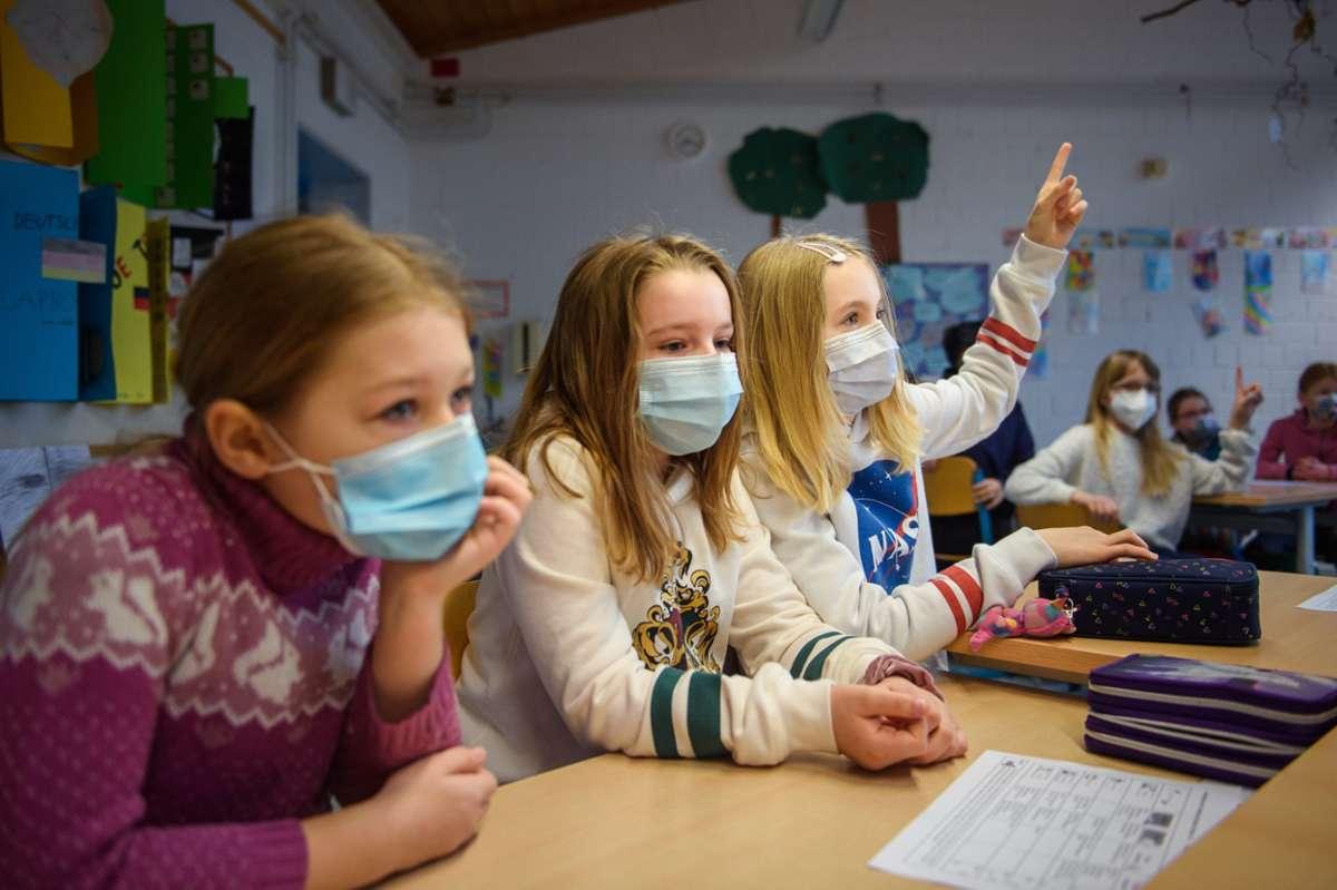 Grundschüler sitzen mit Masken im Unterricht. Foto: Fischer