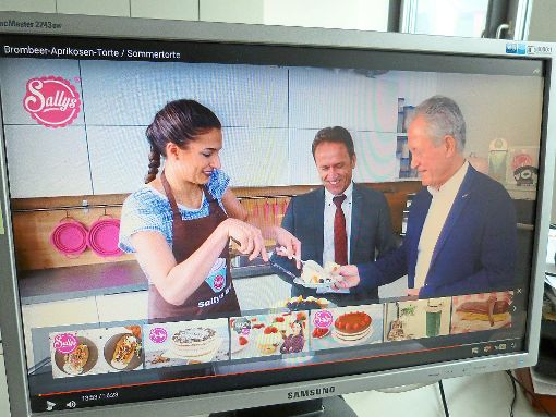 Bürgermeister Hermann Acker (Mitte) und der Erste Beigeordnete Lothar Kopf statten Sally einen Besuch ab und lassen sich vor laufender Kamera ein Stückchen Kuchen munden.   Foto: Screenshot Youtube