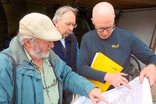 Martin Seeger informiert anhand einer Karte Michael Mayle und Jörg Mezger (von links), die Luftunfälle erforschen, wo im Zwerenberger Wald nach der Absturzstelle gesucht werden muss.  Foto: Schabert Foto: Schwarzwälder Bote