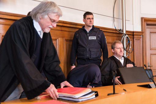 Der Angeklagte Drazen D. (gebückt) mit seinen Anwälten und einem Justizmitarbeiter beim Prozessauftakt. Foto: Graner