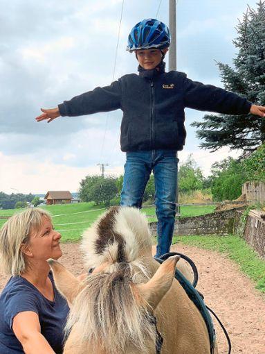 Freihändig auf dem Pferd stehen, Felix Tobler vertraut dabei der Reittherapeutin Patricia Lindecke.  Fotos: Bechtle Foto: Schwarzwälder Bote