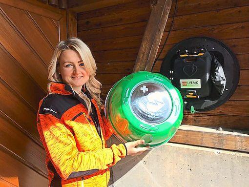 Ramona Rauch  zeigt den neuen Defi außen am Gebäude der Firma Rauch in Bickelsberg.  Foto: May Foto: Schwarzwälder Bote