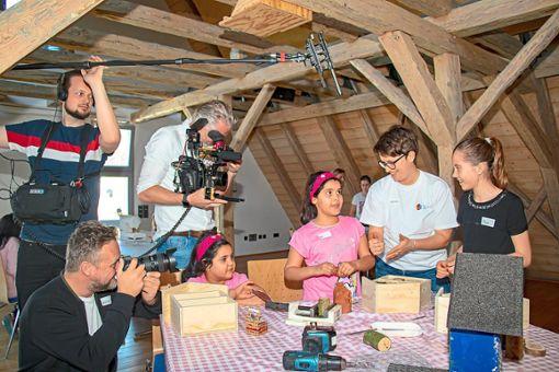 Die Teilnehmer des Workshops im Mehrgenerationenhaus lassen sich von den laufenden Kameras nicht beeindrucken und zeigen, was sie zum Bauen von Insektenhotels gelernt haben. Foto: Geisel