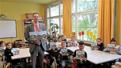 Bürgermeister Marcus Türk, das Kinderbuch Meine Gemeinde, mein Zuhause und Drittklässler der Villingendorfer Grundschule.   Foto: Schule Foto: Schwarzwälder Bote