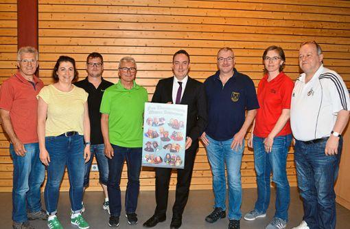Bürgermeister Peter Schumacher (Fünfter von links) und Ortsvorsteher Hermann Hirt (links daneben) freuen sich mit den wieder gewählten Funktionären der FNMS über den Bildband des Narrenrings.  Foto: Herzog Foto: Schwarzwälder Bote