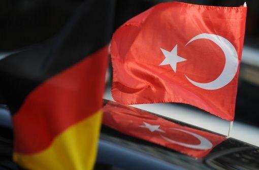 Eine deutsche und eine türkische Fahne wehen an einem Auto Foto: dpa