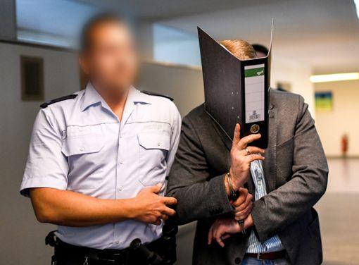 Der wegen Kindesmissbrauchs Angeklagte Knut S. wird von einem Justizbeamten in einen Saal des Landgerichts geführt.    Foto: Seeger