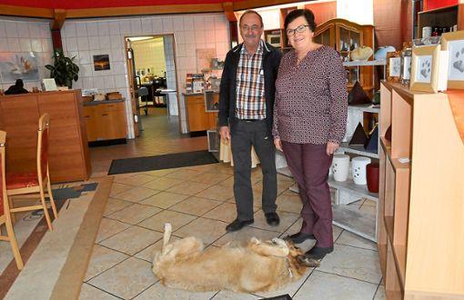 Martina und Claudius Schneider müssen schmunzeln: Hund Timmy will nicht vor der Kamera posieren, er  stellt sich tot. In Wirklichkeit ist der 13-jährige Rüde quicklebendig und schon längst zum Familienmitglied geworden.   Foto: Ungureanu