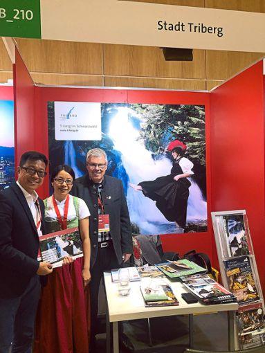 Am Stand der Tourist-Information Triberg  zeigen Thomas Weisser (rechts) und Xiaoqin Rissler (Mitte) einem interessierten Reiseveranstalter aus China die Vorzüge der Schwarzwaldstadt.  Foto: Stadtverwaltung Foto: Schwarzwälder Bote