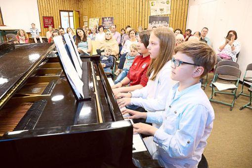 Schülerinnen und Schüler zeigen ihre Fertigkeiten: Senta Bischoff, Nika Pfau und Henri Schäfle spielten zu dritt und ließen alle sechs Hände über die Tasten des Klaviers wandern.  Foto: Wagner Foto: Schwarzwälder Bote