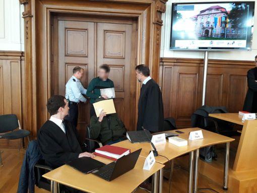 Der Angeklagte Yhad B. (vorne, Mitte) versteckt sein Gesicht, während Mohammed O. (hinten) mit einem Lächeln den Gerichtssaal betritt. Er soll den Horber Unternehmer Michael Riecher getötet haben. Foto: Ganswind
