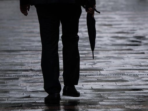 Ein Mann geht mit einem Regenschirm in der Hand. Foto: Andreas Arnold/Archiv/dpa