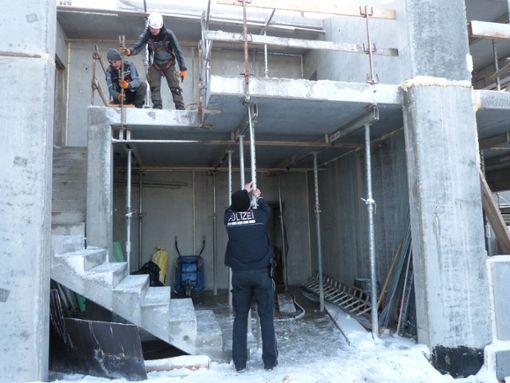 Von der oberen Betonplatte ist der Arbeiter gestürzt. Ein Polizist macht sich ein Bild von der Baustelle. Foto: Merk