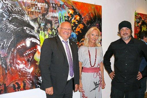 Sie haben sich vor eines der knallbunten Bilder gestellt (von links): Helmut Reitemann, Heidrun Bucher-Schlichtenberger und Mad Matze B.art.L. Foto: Hauser