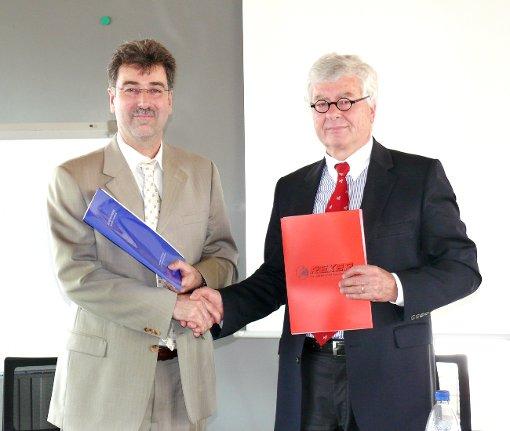 Volker Viniol (rechts) und Arno Ayasse tauschen die Vertragsunterlagen aus.  Foto: Hofmann
