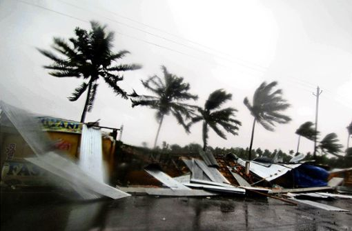 """Geschäfte am Straßenrand sind teilweise zerstört, während der Zyklon """"Fani"""" tobt. Mit Windgeschwindigkeiten von bis zu 195 Stundenkilometern erreichte der tropische Wirbelsturm """"Fani"""" am Freitagmorgen (Ortszeit) die Gegend um die Küstenstadt Puri. Foto: dpa"""