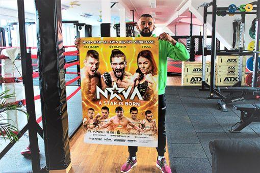 Peter Sobotta hält das Plakat in die Höhe, das für die Mixed Martial Arts-Sport-Veranstaltung wirbt. Zu seiner Überraschung ist sie bereits ausverkauft.  Foto: Breisinger