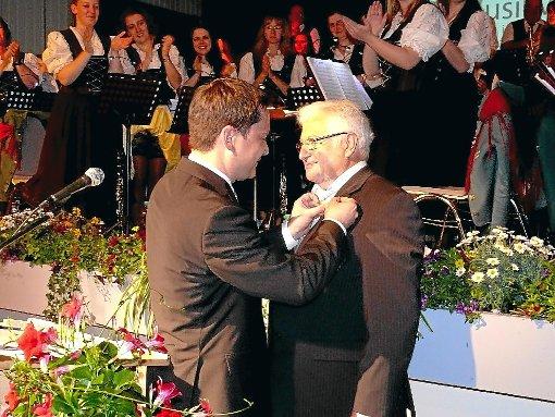 Bürgermeister Klaus Mack (links) heftete dem langjährigen Musikverein-Geschäftsführer Helmut Bürkle die Landesehrennadel an. Foto: Schwarzwälder-Bote