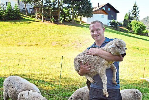 Marcel Zifle mit seinem besonderen Schützling Sunny. Das kleine Schäfchen wurde von Hand aufgezogen.    Foto: Michel