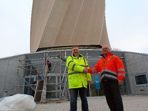 Die Membran ist dran, das letzte Gerüst wird abgebaut:  Projektleiter Hardy Stimmer (links) ist fertig, Turmchef Michael Klein gratuliert. Foto: Otto