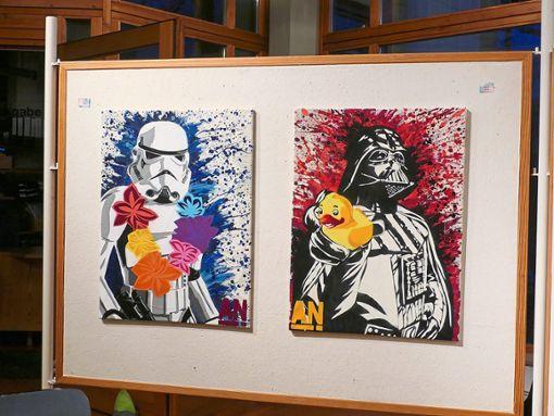 Anika (Ani)  Heimanns (rechts) Sprühdosen-Kunst ist meist mit einem heiteren Augenzwinkern verknüpft. Wer käme schon auf die Idee, Darth Vader aus Krieg der Sterne ein Quietsche-Entchen in die Hand zu drücken? Die Künstlerin aus Balingen freute sich, dass  die Eröffnung ihrer ersten Ausstellung in Bisingen so gut besucht war.  Fotos: Sauppl Foto: Schwarzwälder Bote