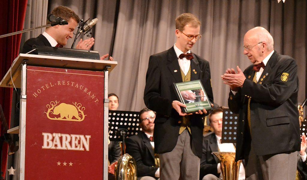 Peter Flaig und Matthias Krause (von links) überreichen dem verdienten Musiker einen Bildband. Foto: Kiolbassa Foto: Schwarzwälder Bote