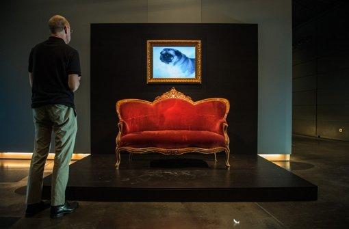 Auf dem roten Sofa hat Vicco von Bülow alias Loriot den TV-Humor revolutioniert. Über dem Sofa steht ein Fernseher auf dem Ausschnitte aus der Serie Cartoon mit Loriot zu sehen sind. Zu sehen ist das Ensemble bis zum 13. September im Haus der Geschichte. Foto: dpa