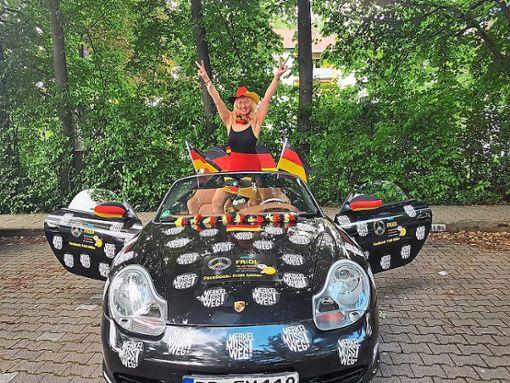 Nein, Fridi Miller bringt sich hier nicht für die bevorstehende Fußball-WM in Position. Ihre  Botschaft gegen Kanzlerin Merkel auf dem schwarzen Flitzer ist klar. Foto: Miller