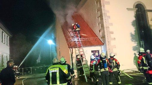 Über eine Steckleiter sind die Atemschutzträger aufs Dach gelangt und decken einen Teil davon ab. Pfarrer Christof Seisser (links) beobachtet das Geschehen. Foto: Ungureanu