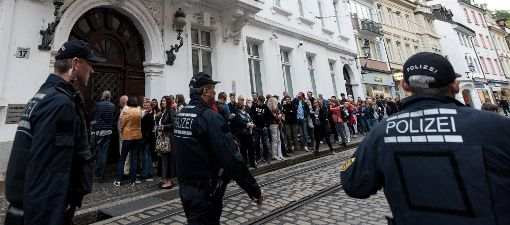 Besucher, Journalisten und Polizisten stehen vor Prozessbeginn vor dem Landgericht Freiburg. Foto: dpa