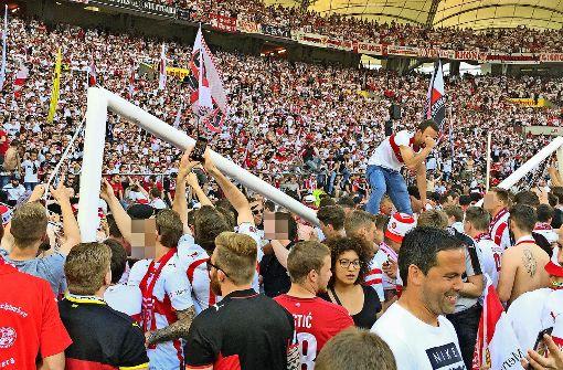 Die Fans stürmen den Rasen und holen sich ein Stück vom Fußballglück: Die Tore im Stadion müssen dran glauben. Foto: Markus Merz, Robin Rudel,  Lg/Piechowski (2)
