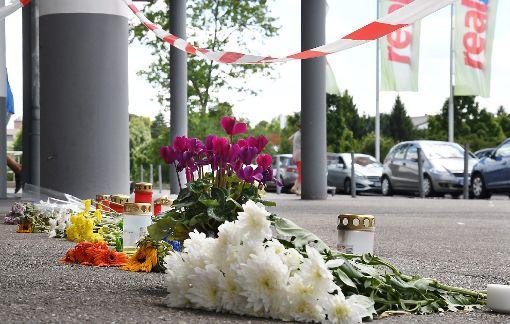 Blumen  vor dem Real-Markt bezeugen die Trauer und Anteilnahme: Am Donnerstag wurde ein 33-jähriger Familienvater erstochen. Foto: Hopp
