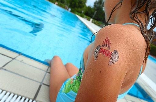 Ein Mädchen mit einem »NO!«-Klebetattoo am Arm im Freibad von Tettnang. Foto: Hildenbrand