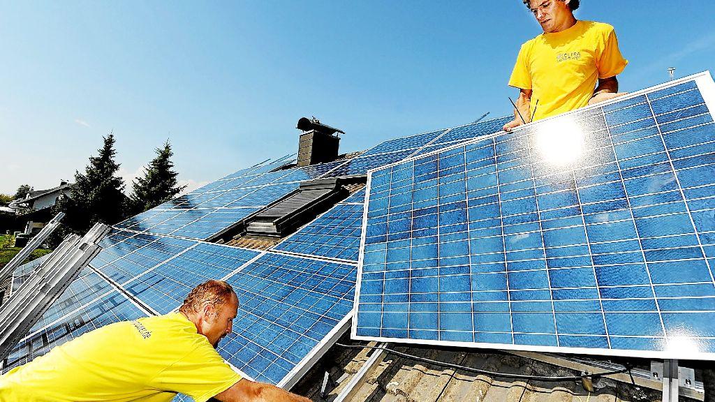 zwei arbeiter montieren auf dem dach module f r eine fotovoltaikanlage die nutzung der. Black Bedroom Furniture Sets. Home Design Ideas