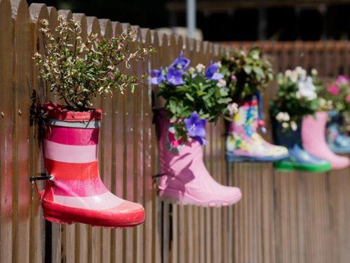 Gummistiefel mit Blumen hängen am Zaun eines Kindergartens. Foto: Julian Stratenschulte/Archiv/dpa