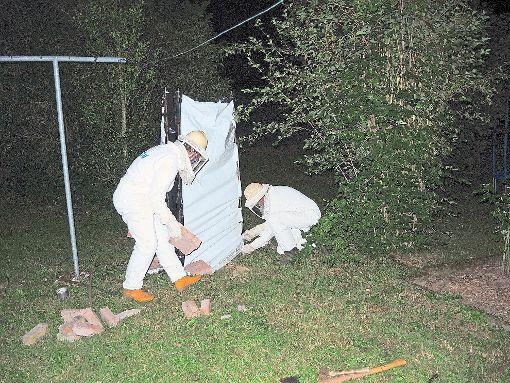 Zu zweit in Schutzanzügen  wird ein Schornstein in dem Garten errichtet. Ein Teil der Plane wird als Schürze am Boden mit Steinen beschwert. Ein betroffener Anwohner hilft dem Experten Lothar Krikoski dabei.   Foto: Jehle Foto: Schwarzwälder-Bote