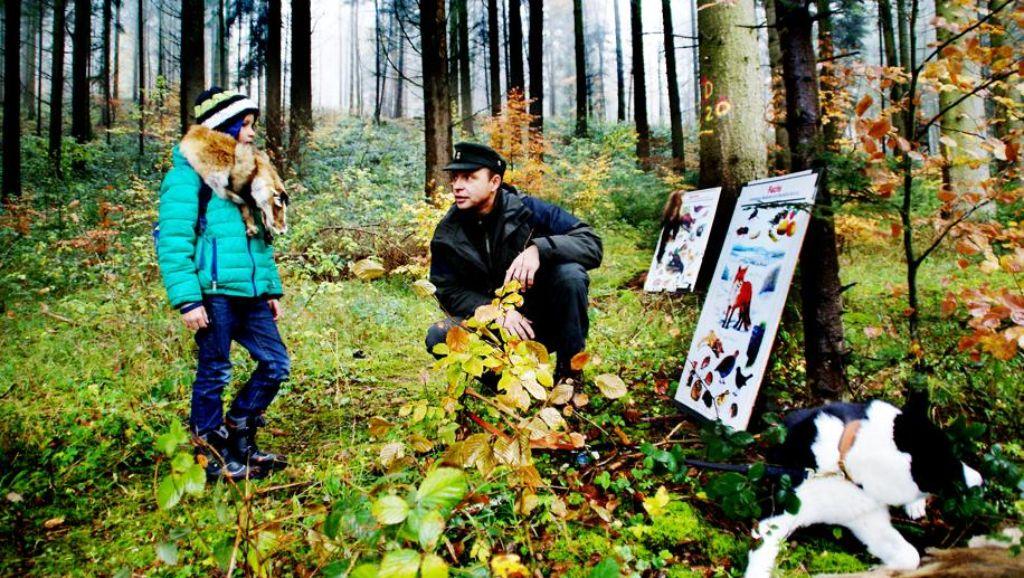 Jäger Viktor Kiefel sitzt im Wald vor bunten Schautafeln
