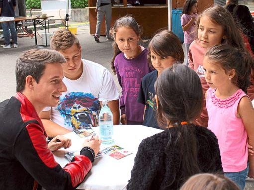 Damiano Maiolini stattet den Kindern einen Besuch ab (links), am Trapez kann man sich durch die Lüfte schwingen, und beim Kick wird alles gegeben. Foto: Schwarzwälder Bote
