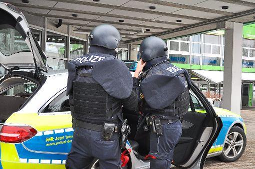 Polizisten legen vor dem Schulzentrum ihre Schutzausrüstung an.   Foto: Müller