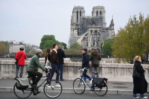 Fußgänger und Radfahrer betrachten die Kathedrale Notre-Dame am Tag nach dem Brand. Foto: Victoria Jones/PA Wire/dpa