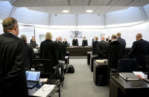 Teilnehmer am Prozess im Landgericht Stuttgart stehen vor Prozessbeginn im Gerichtssaal. Foto: Schuldt