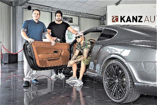 Sven und Michael Kanz mit Kay One, der in seinem neuen Bentley sitzt. Foto: Kay One